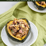 Half of an Acorn Squash stuffed with wild rice and apples on a white plate sitting over a green napkin with the recipe title over the top.