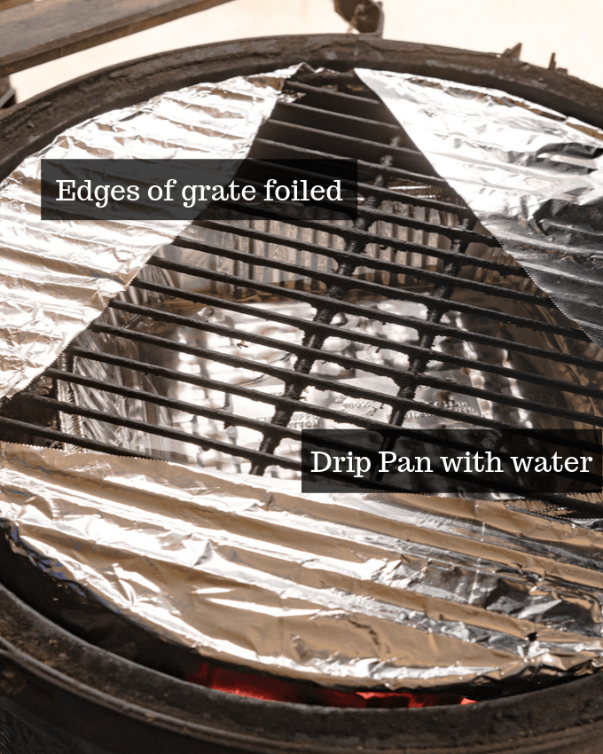 Grill set-up for spatchcocked turkey showing edges covered in foil with an aluminum pan under the grate to collect turkey juices