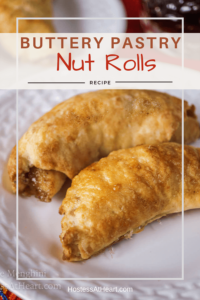 Close up of two baked nut rolls sitting on a white plate.
