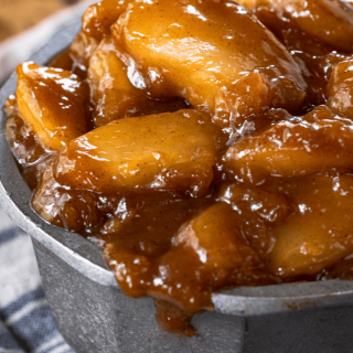 Straight on view of apples in brown sugar-cinnamon sauce overflowing a metal bowl.