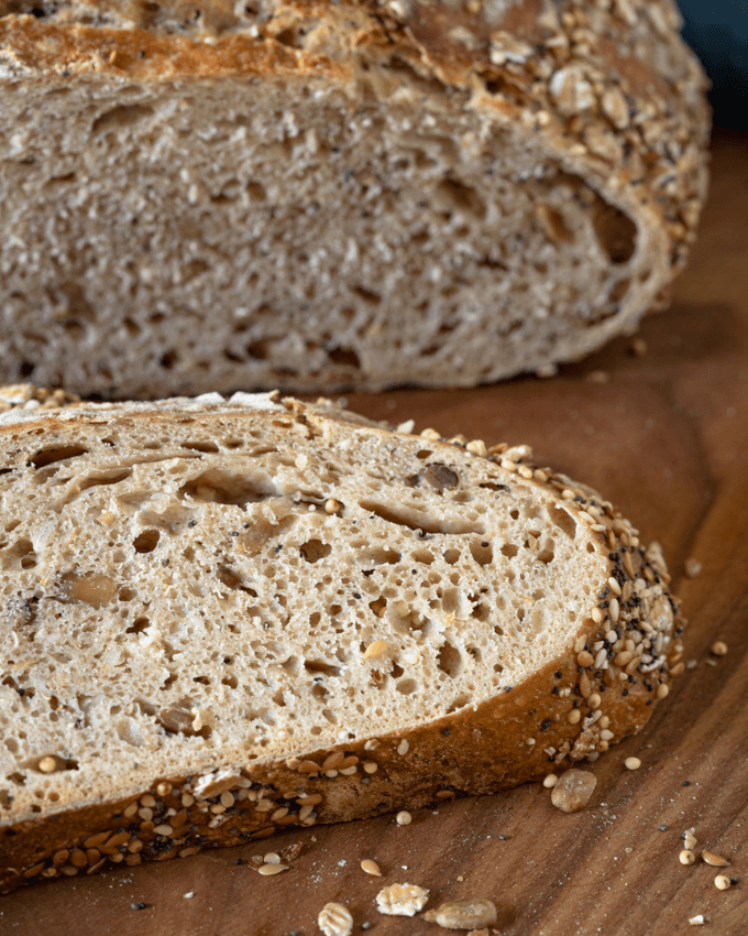 Angled photo of a slice of wheat bread with seeds and oats baked into it in front of the loaf.
