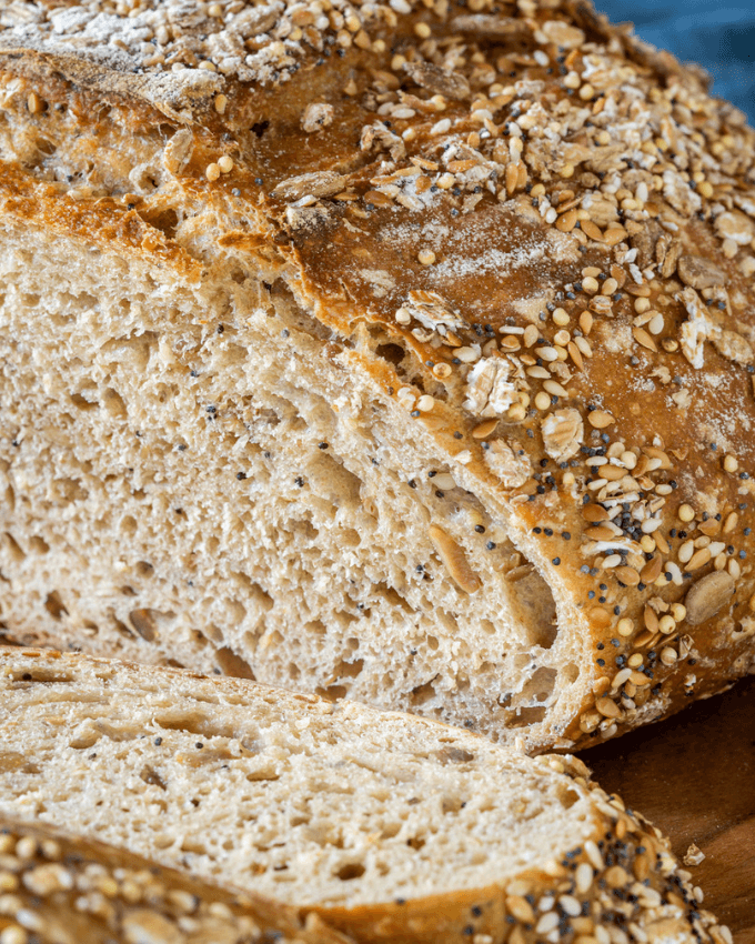 Close-up photo showing the holes in the crumb and a browned crusty exterior topped in a multi-grain blend of seeds and oats.