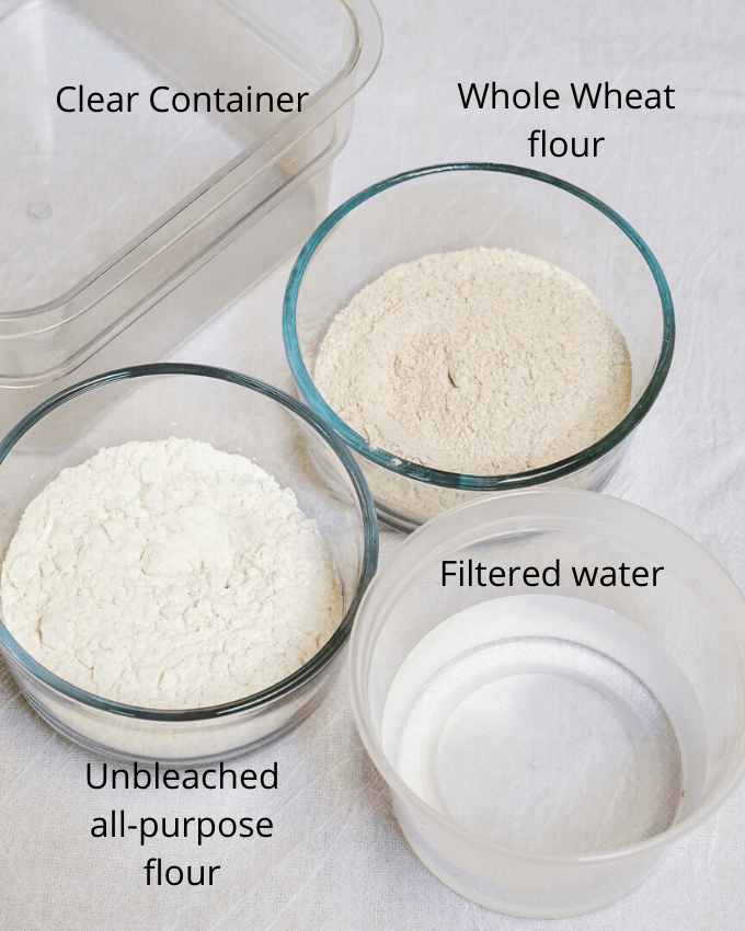 two bowls of flour, a bowl of water and a mixing bowl