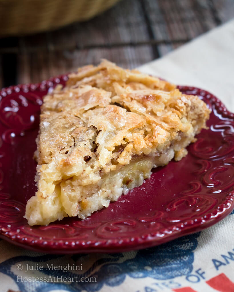 A slice of Swedish apple pie with a flaky top on a red plate.