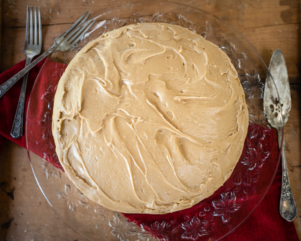 Top down view of a round layered cake on a glass platter over a red napkin on a wooden board. Antique cake servers and forks sit beside the cake.