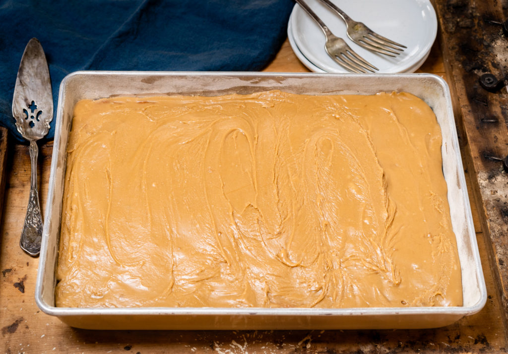 Top angled view of a 9x13 cake frosted with caramel icing sitting on a wooden board. Two serving plates with forks and a blue napkin sits behind it.