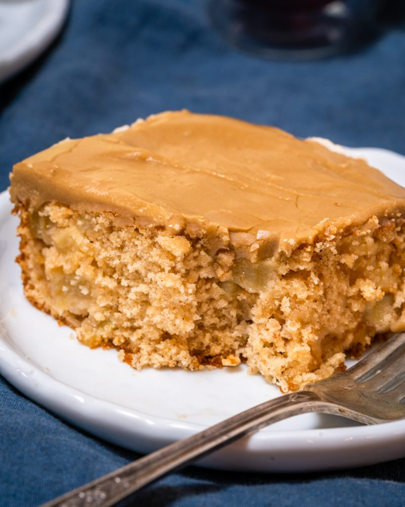 A slice of cake with a bite taken out of it showing chunks of apples inside and frosted with a caramel icing.