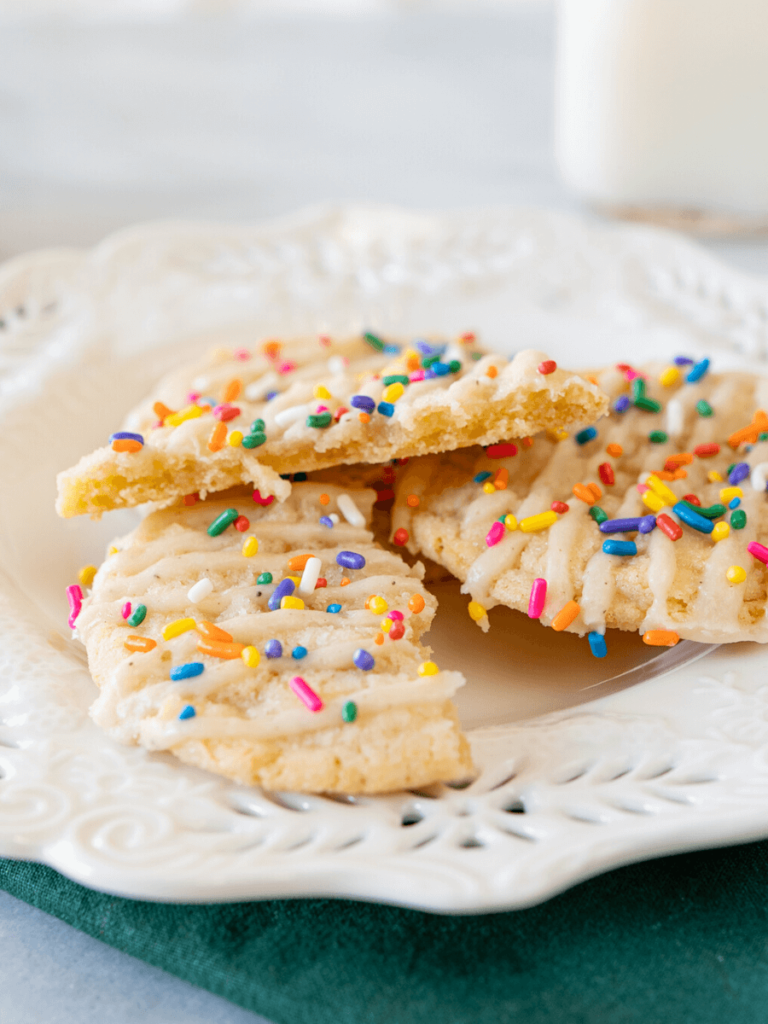 Close up side photo of a broken glazed cookie with sprinkles on a white plate showing the soft center.
