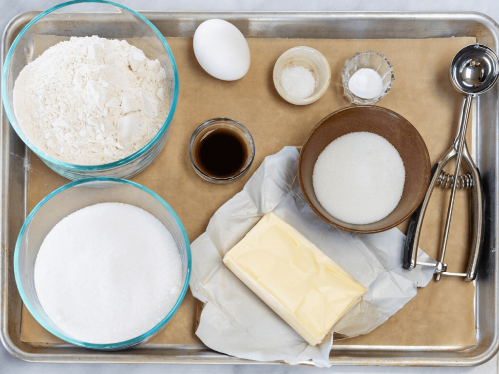 Cookie tray filled with the ingredients necessary to make sugar cookies. Flour, sugar, butter, egg, vanilla, baking soda and salt next to a dough scoop.