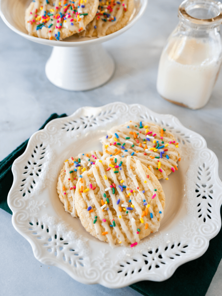Top shot of 3 glazed and sprinkled cookies on a white plate in front of a bottle of milk and a pedestal dish with more cookies.