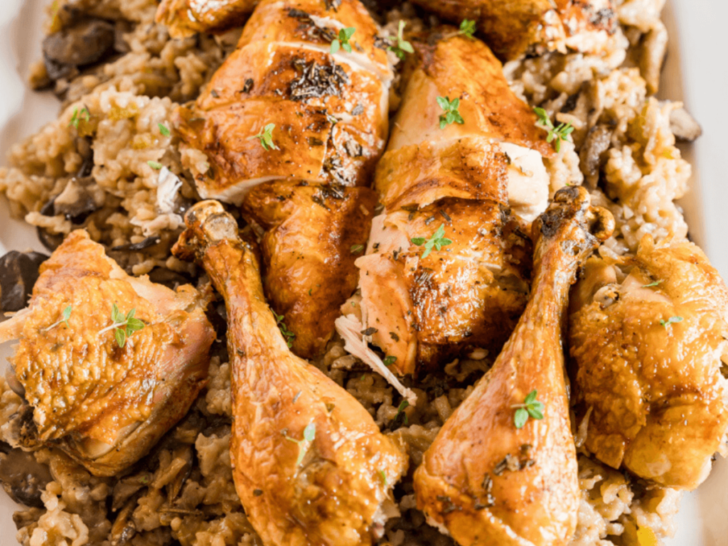 Close up top view of roasted chicken sitting on a creamy bed of mushroom risotto and garnished with fresh thyme leaves