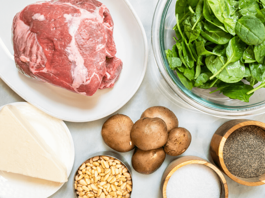 Top down view of the ingredients used to make lamb roulade. Leg of lamb, spinach, mushrooms, cheese, and pine nuts.