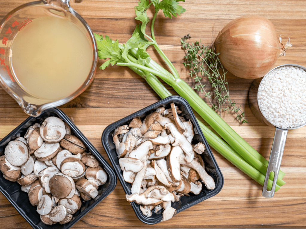 Ingredients for mushroom risotto including chicken stock, celery, onion, mushrooms, rice and fresh thyme