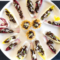 Top view of a round white platter filled with endive lettuce leaves and phyllo cups filled with lamb bits, pecorino cheese and fresh thyme
