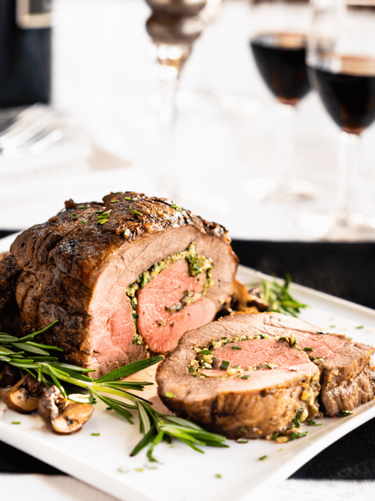 Straight on view of a roasted lamb roulade stuffed with a filling of pine nuts, cheese, mushrooms, and spinach on a white plate surrounded by mushrooms and rosemary sprigs.