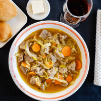Top down photo of a bowl of vegetable lamb soup in a white bowl sitting on a black placemat. A glass of wine and plate of bread and butter sit behind it.