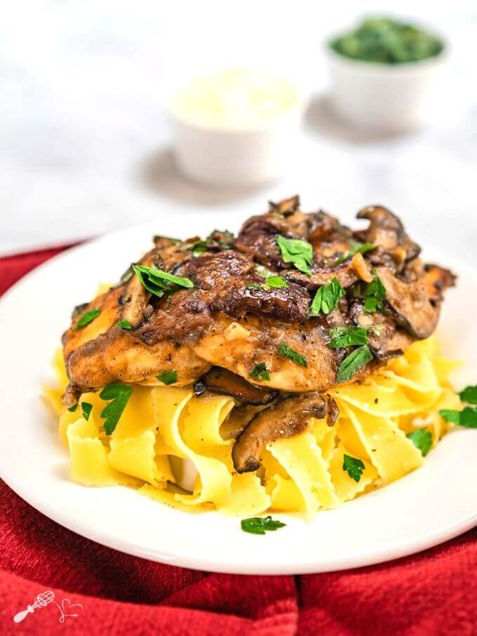 Side view of a dish of browned chicken breasts on a bed of egg noodle pasta covered with a creamy mushroom marsala sauce and garnished with parsley in a white bowl sitting on a red napkin. with small dishes of parsley and cheese in the background.