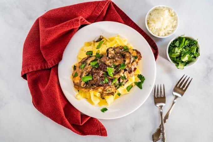 Top down view of a dish of browned chicken breasts on a bed of egg noodle pasta covered with a creamy mushroom marsala sauce and garnished with parsley in a white bowl sitting on a red napkin. with small dishes of parsley and cheese in the background.