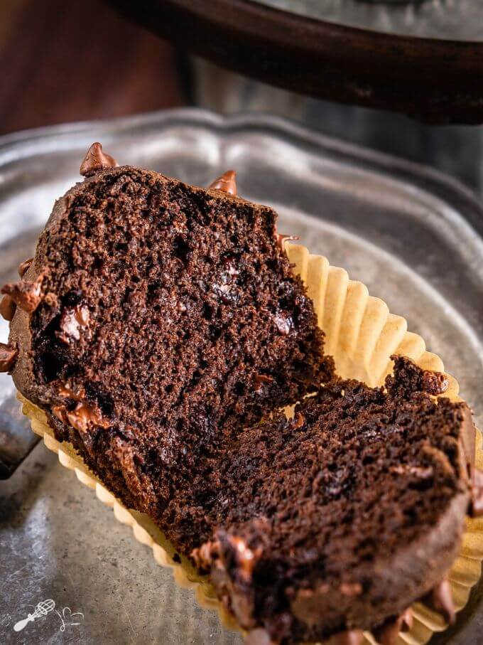 Double Chocolate Muffin sliced in half showing a soft inner crumb and melted chocolate chips. The muffin sits in a tan muffin paper on a silver tray.