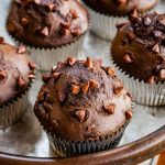 Silver pedestal tray topped with a double chocolate muffin with chocolate chips on top in front of 4 out of focus muffins.