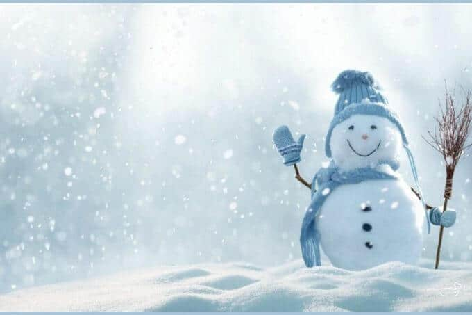 Photo of a snowman dressed in a blue hat, gloves, and a scarf holding whisk broom and standing in the snow with a smile on his face.