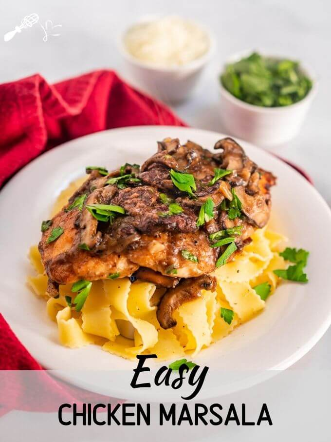 "Angled view of a dish of browned chicken breasts on a bed of egg noodle pasta covered with a creamy mushroom marsala sauce and garnished with parsley in a white bowl sitting on a red napkin. Small dishes of parsley and cheese in the background and the title banner ""Easy Chicken Marsala Recipe\"" runs across the bottom."