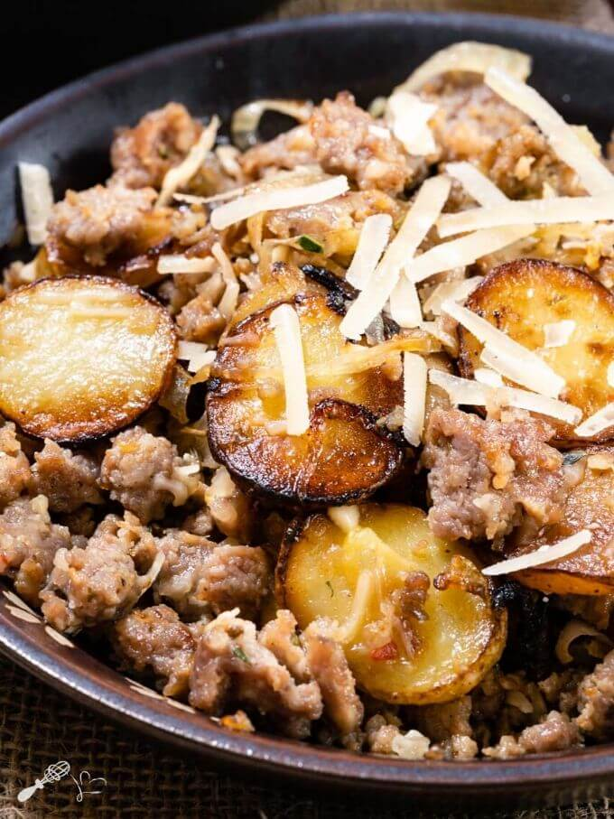 Top down photo of sausage and fried potatoes sprinkled with parmesan cheese in a brown bowl.