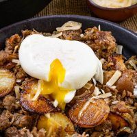 Top down photo of sausage and fried potatoes sprinkled with parmesan cheese with a soft cook egg pouring over it.