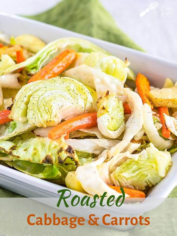 """White baking dish filled with roasted green cabbage, orange carrots, apples, and onions with a silver serving spoon in the pan sitting on a green napkin. The title \""""Roasted Cabbage and Carrots with Apple\"""" runs across the bottom."""