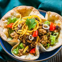 Top angel view of a taco bowl filled with spicy ground chicken and black bean filling topped with shredded cheese, lettuce and tomatoes on a green napkin.