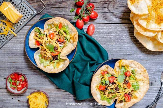 Top down view of two taco bowls loaded with ground chicken, black beans and lettuce garnished with tomatoes, cilantro and shredded cheese on a green napkin. Small bowls of cheese and diced tomatoes sit off to the side.