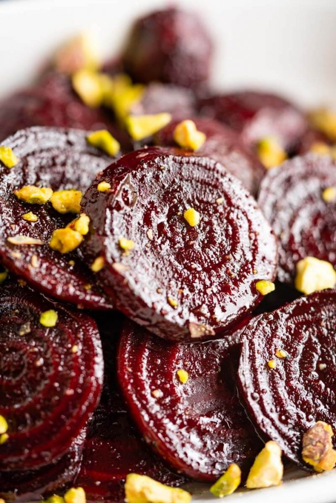Close-up side-angle photo of glistening red beet slices in a white bowl sprinkled with chopped pistachio nuts.
