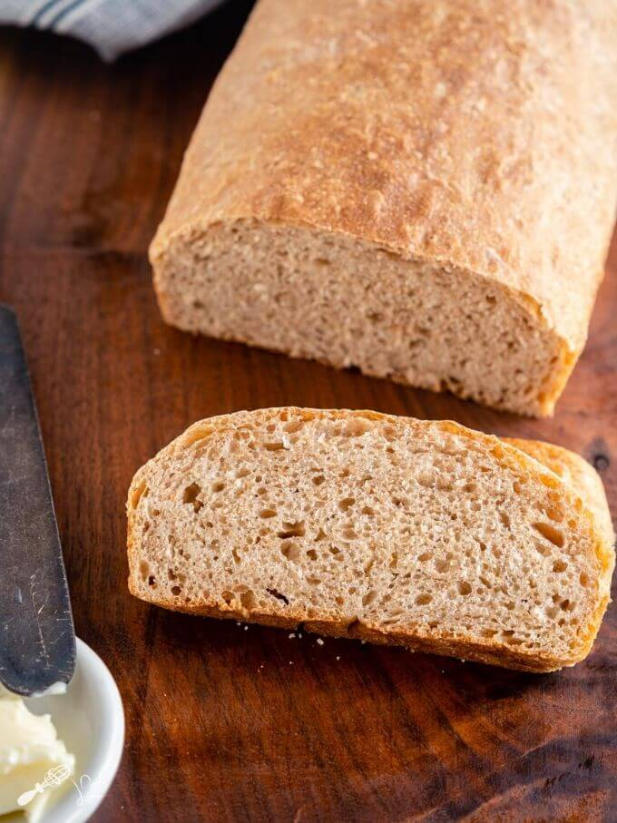 A partial loaf of spelt bread with a slice of bread sitting in front of it on a wooden cutting board. A butter knife and dish of butter sit to the side.