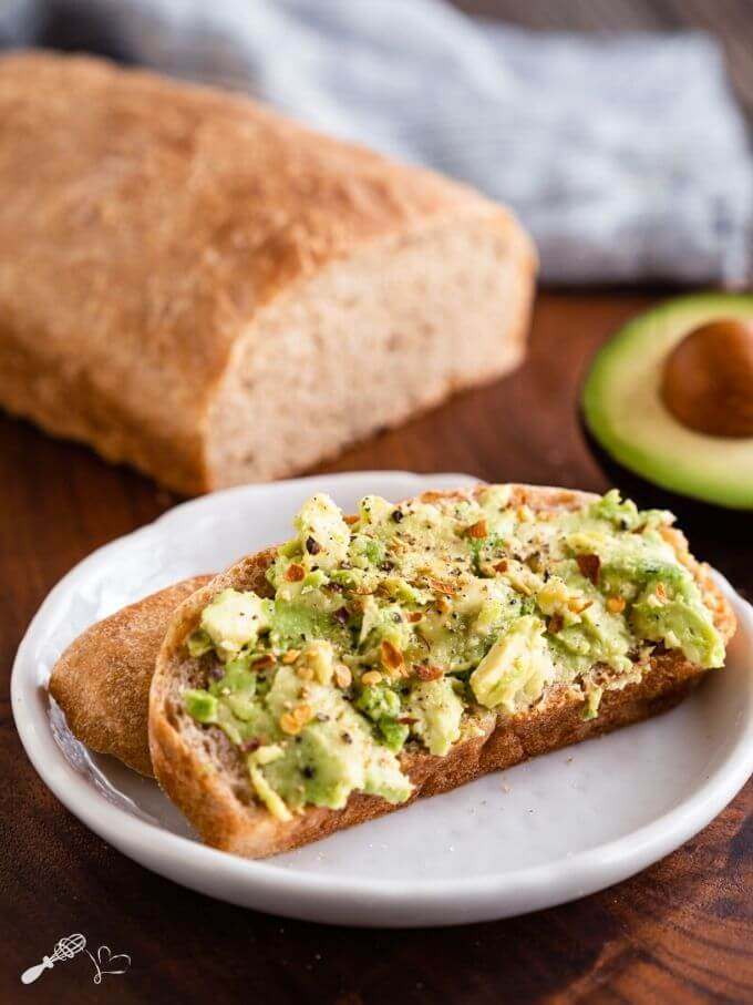 A slice of avocado toast sitting on a white plate over a wooden cutting board. A cut loaf of bread and half of an avocado sit in the background.
