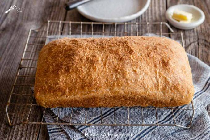 A loaf of browned spelt bread sitting on a cooling rack over a blue striped napkin and wooden background. A pat of butter in a white dish and a white plate sit behind it.