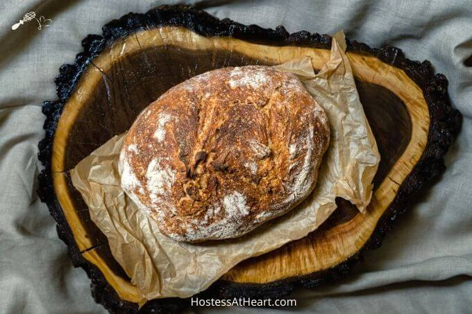 Top down photo of a loaf of beautifully browned spelt bread sitting on natural parchment paper and a wooden background.