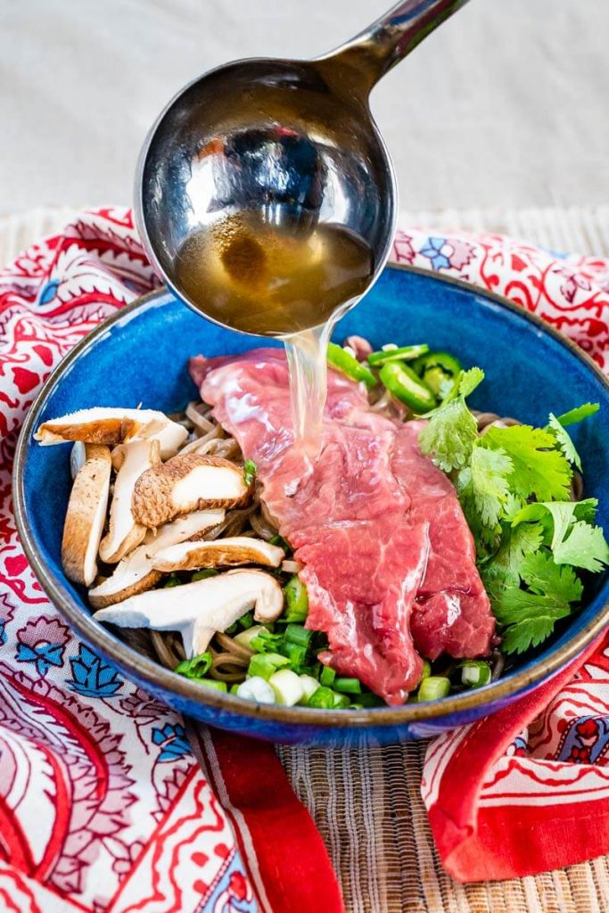 Hot pho broth is being ladled over sliced raw lamb, sliced mushrooms, green onions, Serrano peppers, cilantro, and buckwheat noodles sitting in a blue bowl on a multicolored napkin and grass-cloth placemat.