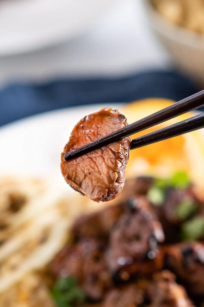 A cooked piece of lamb glazed in orange marinade being held with a pair of chopsticks over a blurred serving of lamb kabobs on brown rice.