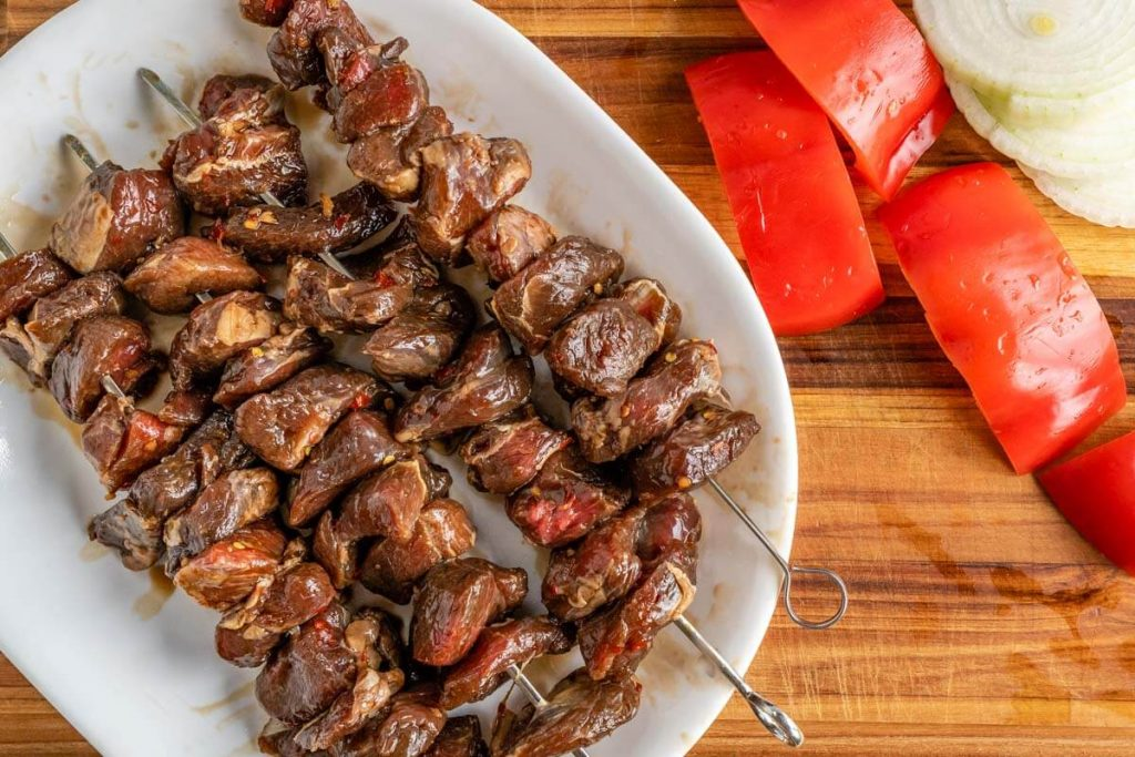 Top down view of skewers filled with marinated chunks of lamb on a white plate next to a chopped red pepper and sliced onion. It all sits on a wooden cutting board.