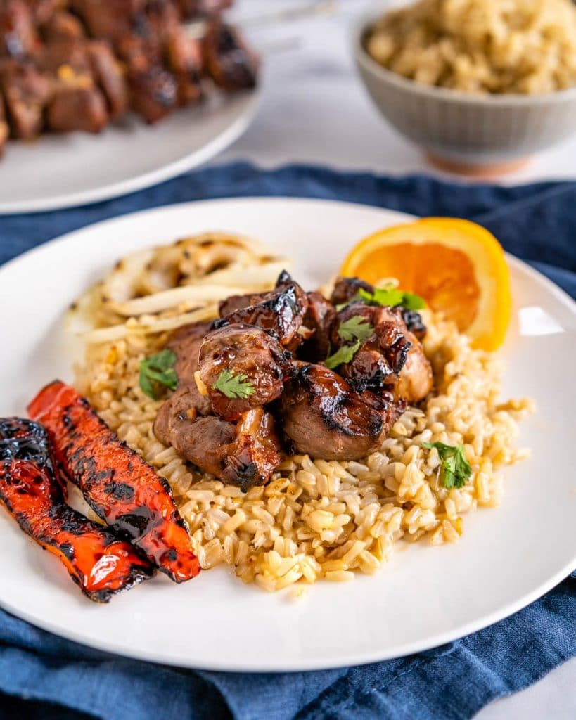 Close-up angle view of chunks of lamb kabob drizzled in an orange glaze sitting on brown rice. Roasted red peppers sit next to the rice on a white plate. A plate of grilled kabobs and a bowl of rice sit in the background.