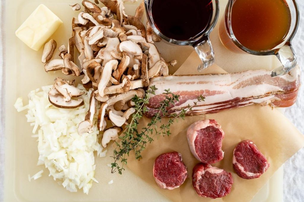 A white cutting board filled with chopped onion, mushrooms, 4 lamb medallions, 4 strips of bacon, 4 tablespoons of butter, fresh thyme, a cup of red wine and a cup of beef broth.