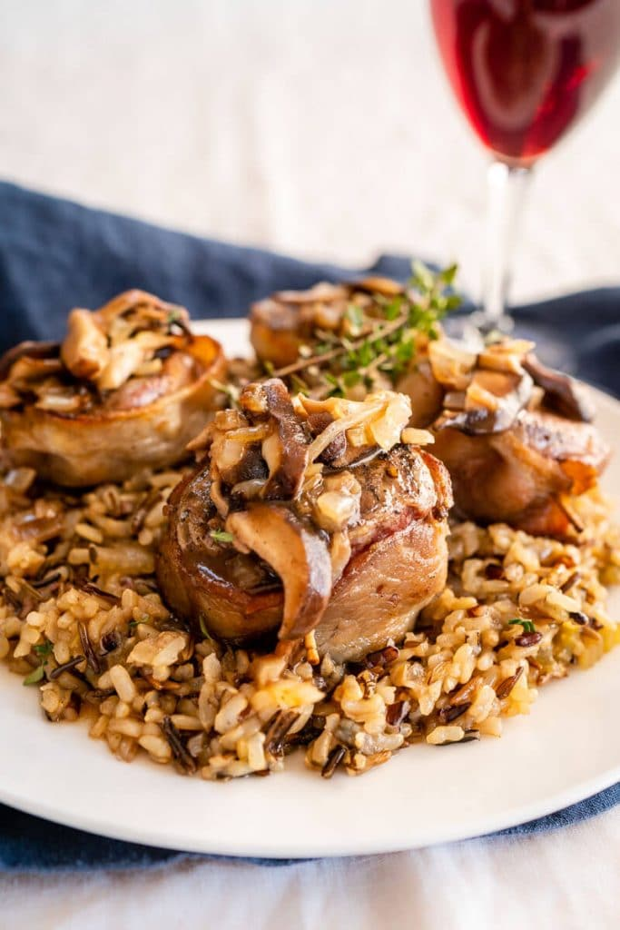 Close-up side view of a white plate with wild rice in the center topped with 4 bacon-wrapped lamb medallions covered in a wine sauce with mushrooms. A sprig of thyme garnishes the dish.