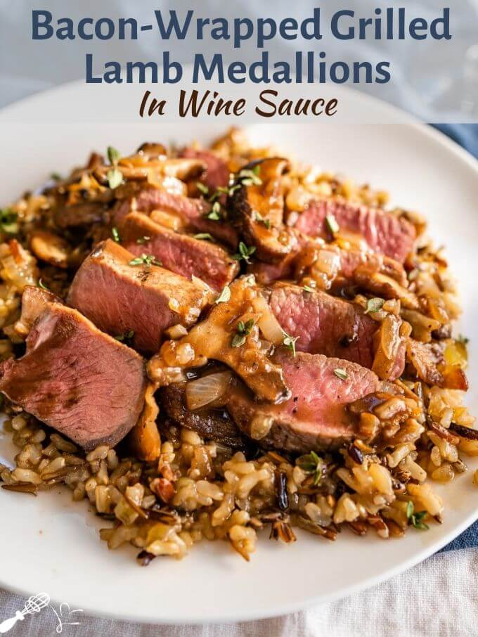"A white plate of medium-rare sliced lamb medallions on a bed of wild rice with a wine sauce drizzled over the top. The title ""Grilled Aussie Lamb Medallions in Red Wine Sauce\"" banner runs across the top of the photo"