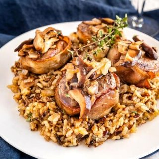 White plate with wild rice in the center topped with 4 bacon-wrapped lamb medallions covered in a wine sauce with mushrooms. A sprig of thyme garnishes the dish.