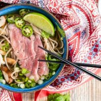 Top down shot of garnishes used in our homemade pho including raw lamb, mushrooms, cilantro, sliced green onions, Serrano peppers, and buckwheat noodles in a blue bowl on a multicolored napkin.. A pair of chopsticks sit to the side and a bowl of sriracha sits in the back.