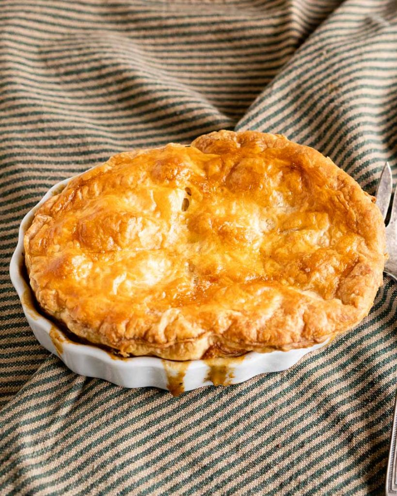 A Lamb pot pie topped with a golden puff pastry crust baked in a white ramekin with the filling dribbling down the sides. The dish sits on a green striped napkin.