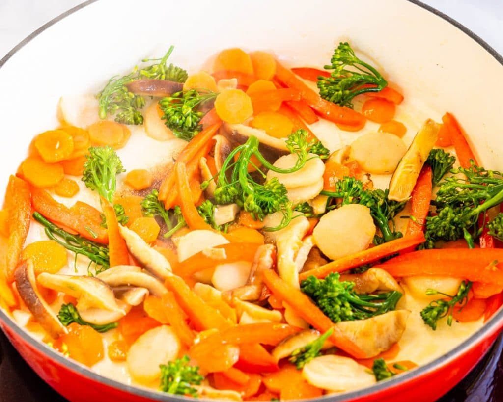 Red dutch oven filled with stir fry vegetables including carrots, water chestnuts, broccolini, and red peppers.