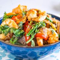 A side view of a blue bowl filled with rice topped with a shrimp stir fry containing broccolini, red peppers, mushrooms, carrots and water chestnuts in a stir fry sauce garnished with fresh cilantro and sitting on a napkin decorated with blue and green designs. A red pan sits in the background.
