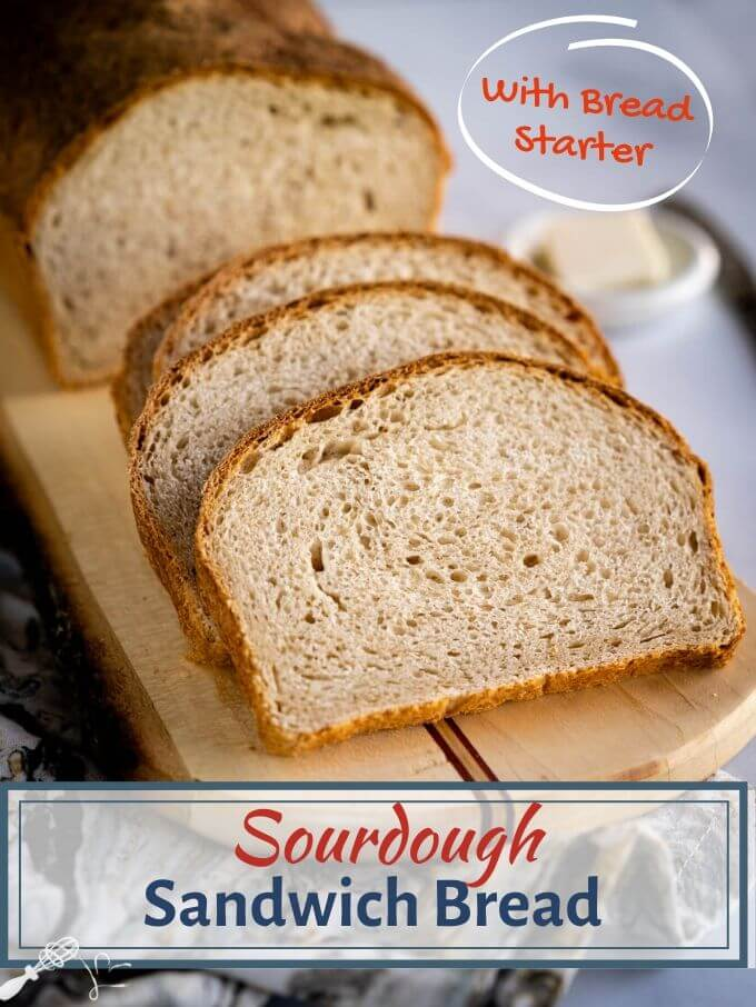 "A sliced loaf of Sourdough Sandwich bread on a cutting board with the title ""Sourdough Sandwich Bread\"" running through the bottom."