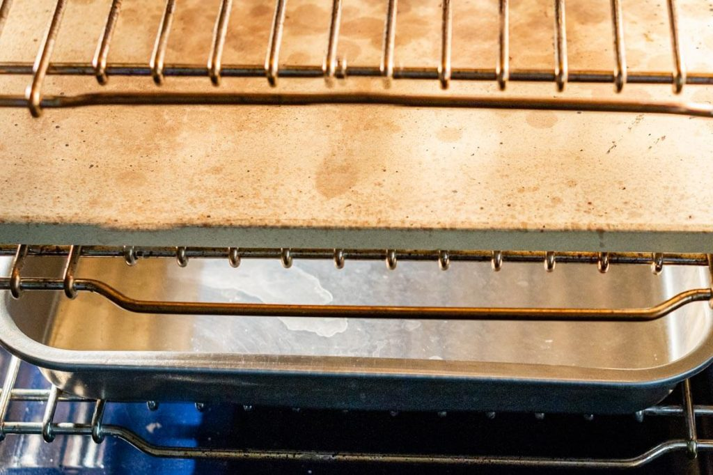 Photo showing how the oven is set up for baking sourdough sandwich bread. The middle grate holds a baking stone and the lower grate holds a broiler pan.